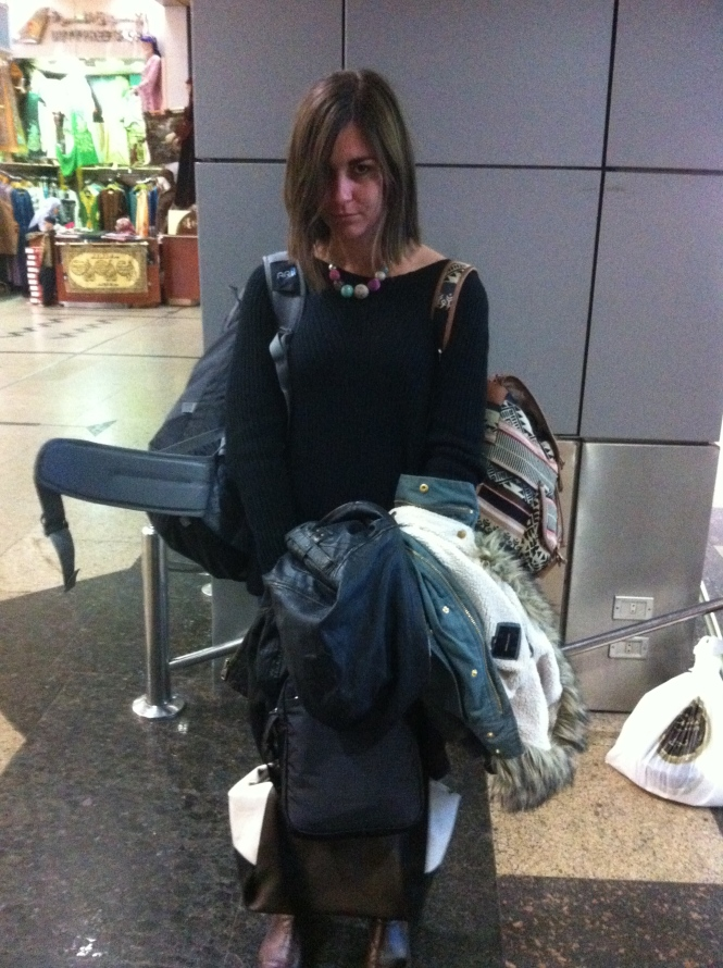 Kara looking 'stabby' holding all of her, and Sam's, carry-on at the airport.